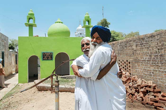 Safe Custody: Joga Singh with a maulvi outside the mosque in Sarwarpur that his brother Sajjan helped reconstruct