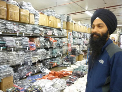Gurdip Singh Malik mulls through a melange of vibrant garments littering his stockroom